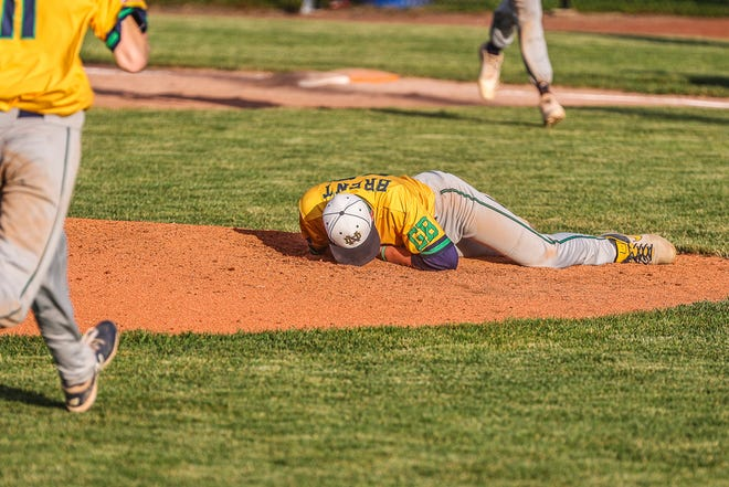 Notre Dame High School junior Jackson Brent lays on the mound after being hit in the lower jaw by a line drive during a baseball game against New London on June 7 at Winegard Field.
