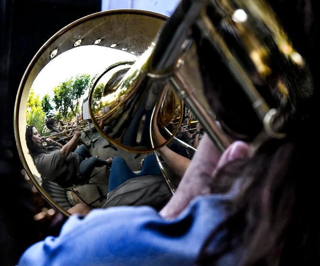 Members of the trombone section are reflected in one of the bells Friday during the weekly Garden City Municipal Band concert in the Stevens Park bandshell.  This year's band will have a shorter season this summer, with the final concert being on July 4 at Lee Richardson Zoo.  The band, which features musicians from several area towns besides just from Garden City this year, has been in existence since 1879.
