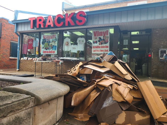 A pile of water-damaged boxes sits in front of Tracks, which lost thousands of dollars of merchandise and equipment to flooding.