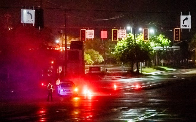 An Indiana University police officer directs traffic while another lights flare to notify drivers that the traffic lights are out at the corner of the Ind. 46 Bypass and East Third Street in the early morning hours Saturday. Severe weather knocked out electricity including several traffic lights as well as caused flooding through the city.