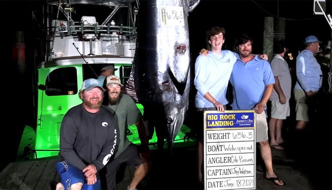 Angler Cole Pirrung, second from right, embraces Captain Jay Watson, as the crew of the WideSpread stand with their 656.5-pound marlin late Friday night at the Big Rock Blue Marlin. [Big Rock Photo]