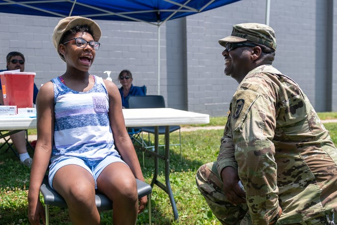 Onnestee Adams talks with Staff Sgt. Gregory Shaw before receiving a COVID-19 vaccine during a Juneteenth event at John H. Gwynn Jr. Park in Peoria on Saturday, June 19, 2021.