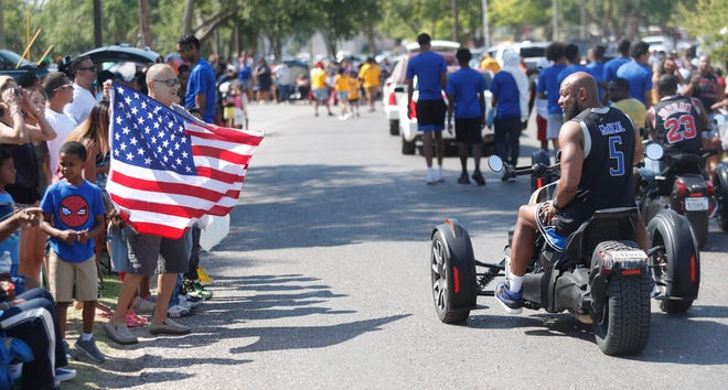 Hector Perez waves an American Flag during the Juneteenth Parade at Mackenzie Park Saturday morning June 19, 2021.