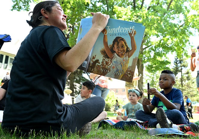 Children listen as Teona Brown, of Marlborough, reads a book about Juneteenth during One Marlborough's second annual Juneteenth Celebration on Union Common in Marlborough, June 19, 2021. The children's book was later raffled off. On Thursday, the federal government recognized Juneteenth as an official holiday marking the end of slavery in the United States. Juneteenth commemorates June 19, 1865, when a Union general reached Galveston, Texas, to inform enslaved African Americans of their freedom.