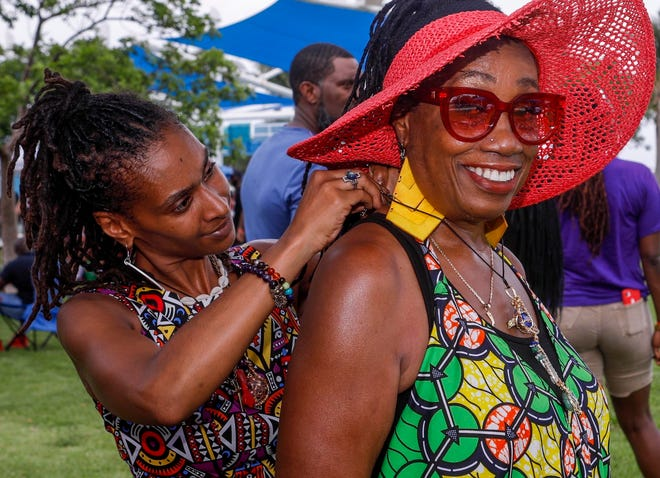 Tamika Peters, the owner of Feeling & Healing, places a crystal necklace on around the neck of Denise Jones during a Juneteenth festival held at the Riviera Beach Marina Village, June 19, 2021. The event was free to the public and featured food, music from X102.3, local vendors, and fun and games for kids.