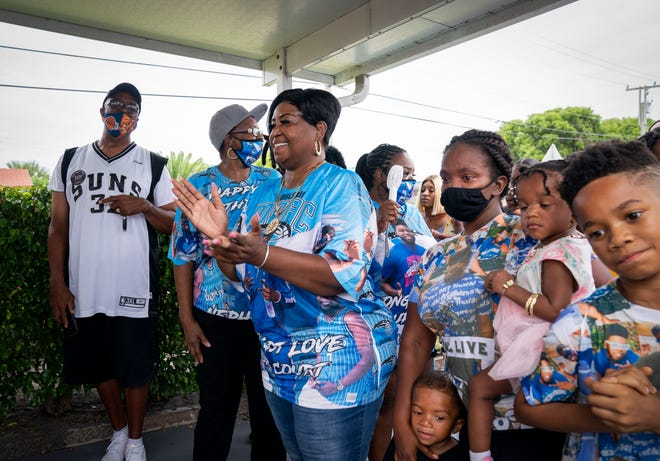 Ramona Fobbs, center, is joined by family and friends for the opening of the Courtney Fobbs Learning Academy in Riviera Beach on Friday.