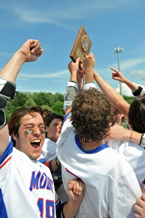The Mount St. Charles boys lacrosse team celebrates with the Division IV championship plaque after Saturday's win over North Smithfield.