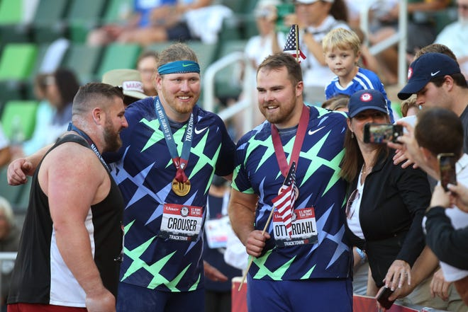 Shot put Olympians Joe Kovacs, left, Ryan Crouser, center, and Payton Otterdahl pose for fan photos during their victory lap at the U.S. Olympic Track & Field Trials at Hayward Field in Eugene on Friday.