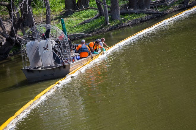 A crew adjusts water booms in the Rock River near a Rockton Road bridge Saturday in Rockton on the sixth day after a massive fire at Chemtool caused evacuations in the town. Officials say there is no sign that any water runoff from fighting the Chemtool fire contaminated the Rock River.