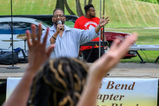 Dennis J. Givens, of New Horizons Outreach Ministry, gives the opening prayer at the Juneteenth celebration at LaSalle Park in South Bend on Saturday.