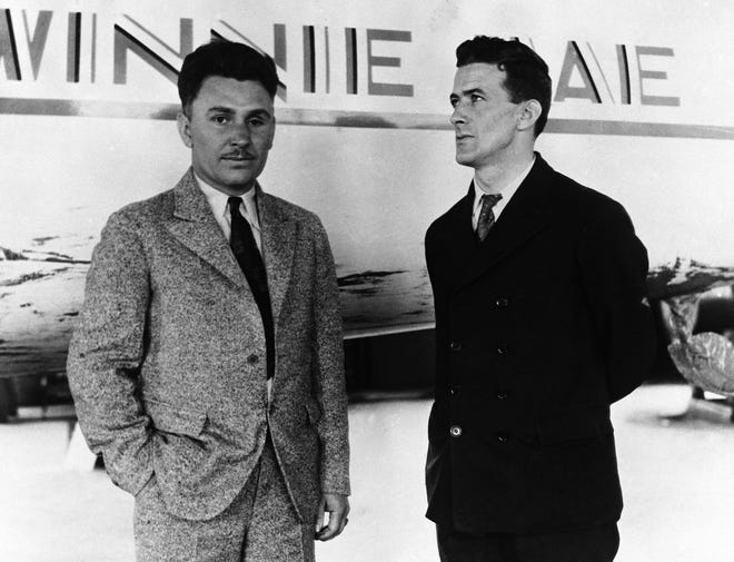 Pilot Wiley Post, left, and his navigator, Harold Gatty, stand in front of their plane, the Winne Mae, before beginning their around the world flight on June 23, 1931.