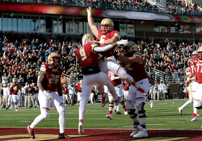 Boston College quarterback Dennis Grosel, top, celebrates his touchdown pass to wide receiver Kobay White (9) against Florida State at Alumni Stadium in Chestnut Hill.