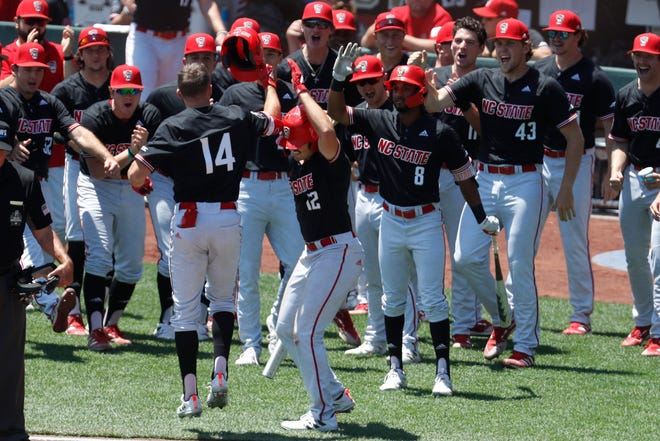 Jun 19, 2021; Omaha, Nebraska, USA;  NC State Wolfpack left fielder Jonny Butler (14) is congratulated by his teammates after hitting a home run against the Stanford Cardinal at TD Ameritrade Park. Mandatory Credit: Bruce Thorson-USA TODAY Sports