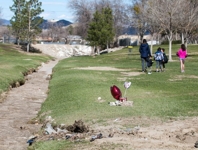 A family walks through Doris Davies Park in Victorville near a memorial set up for Michael Williams, who died there after his car was swept up in floodwaters in February 2017.