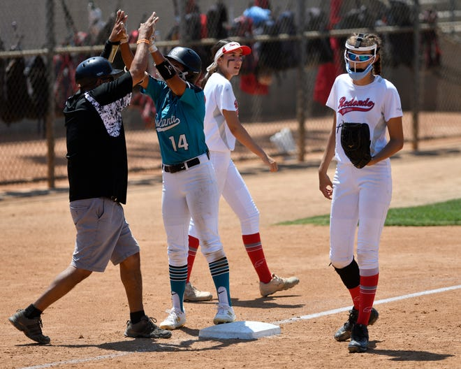 Sultana's Carissa Fillingame celebrates with coach Obie Galindo after hitting a bases-clearing triple against Redondo Union in the CIF-Southern Section Division 3 championship game in Irvine CA on Saturday.