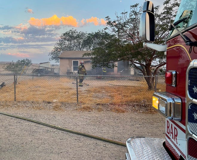 A firefighter stands outside a home where an elderly woman died after becoming trapped during a house fire in Barstow on Friday, June 18, 2021.
