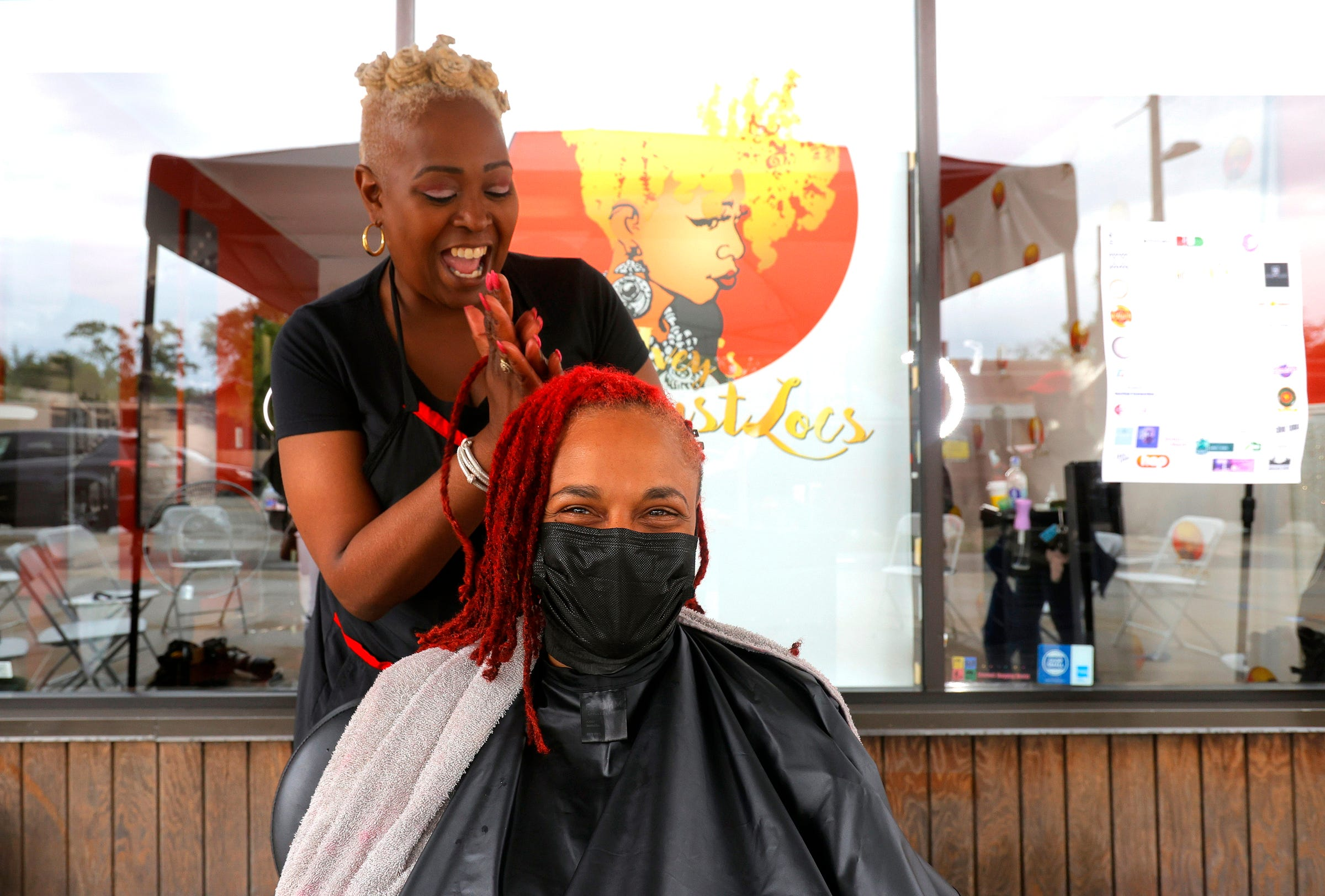 Sala Ivey, 50 of Royal Oak and owner of Knot Just Locs does the hair of long-time client Nichell Fowlkes, 46 of Detroit on the Avenue of Fashion on Livernois in Detroit on June 19, 2021. Ivey and many other business owners on Livernois participated in Juneteenth celebrations as pedestrians walked, window shopped and ate at some of the many restaurants up and down the avenue.