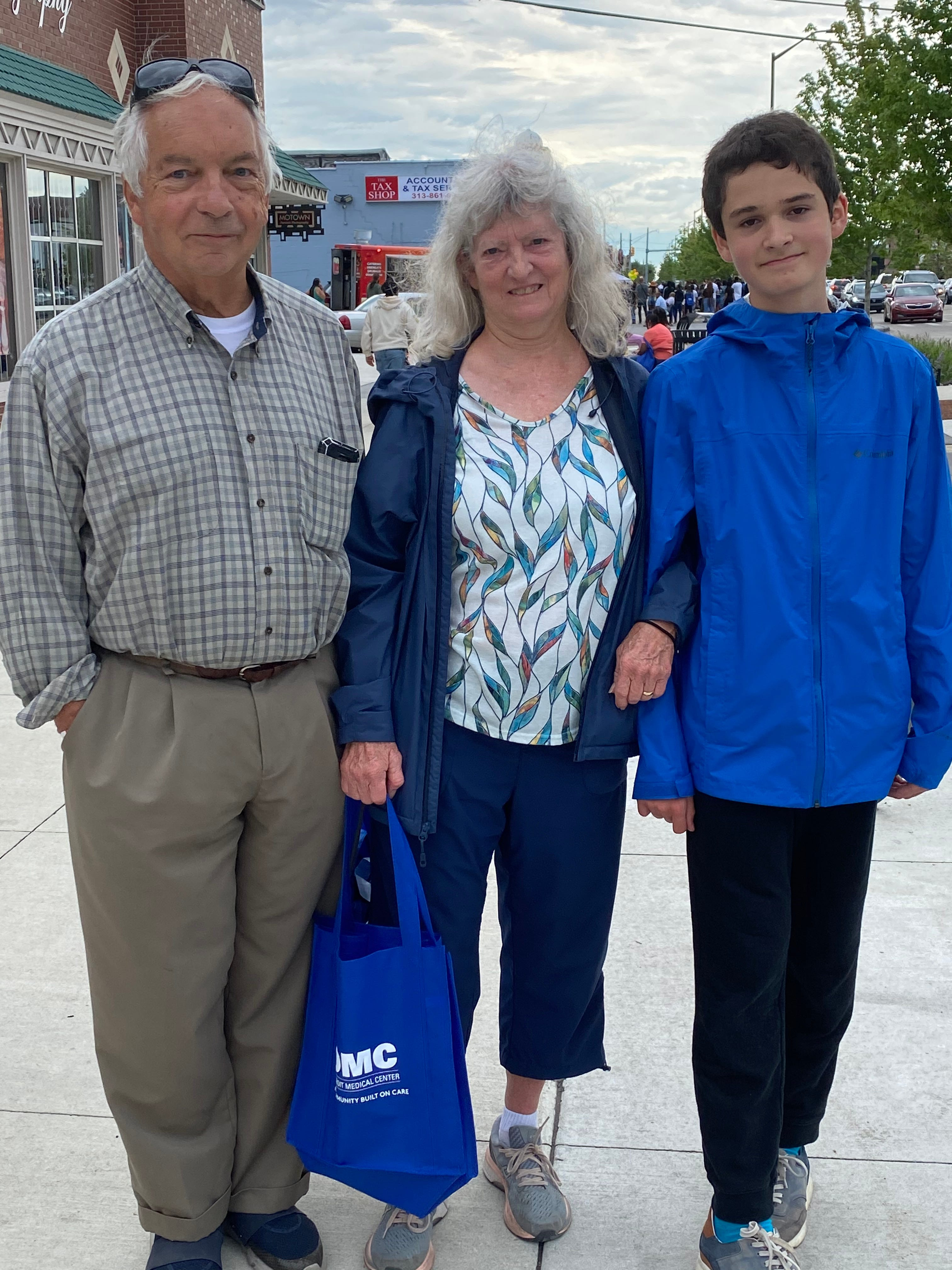 Larry Krupa, 78, Lynn Krupa, 74, and Zen Duran, 14, all pose on the Avenue of Fashion after shopping before catching their flight back home to Portland, OR.