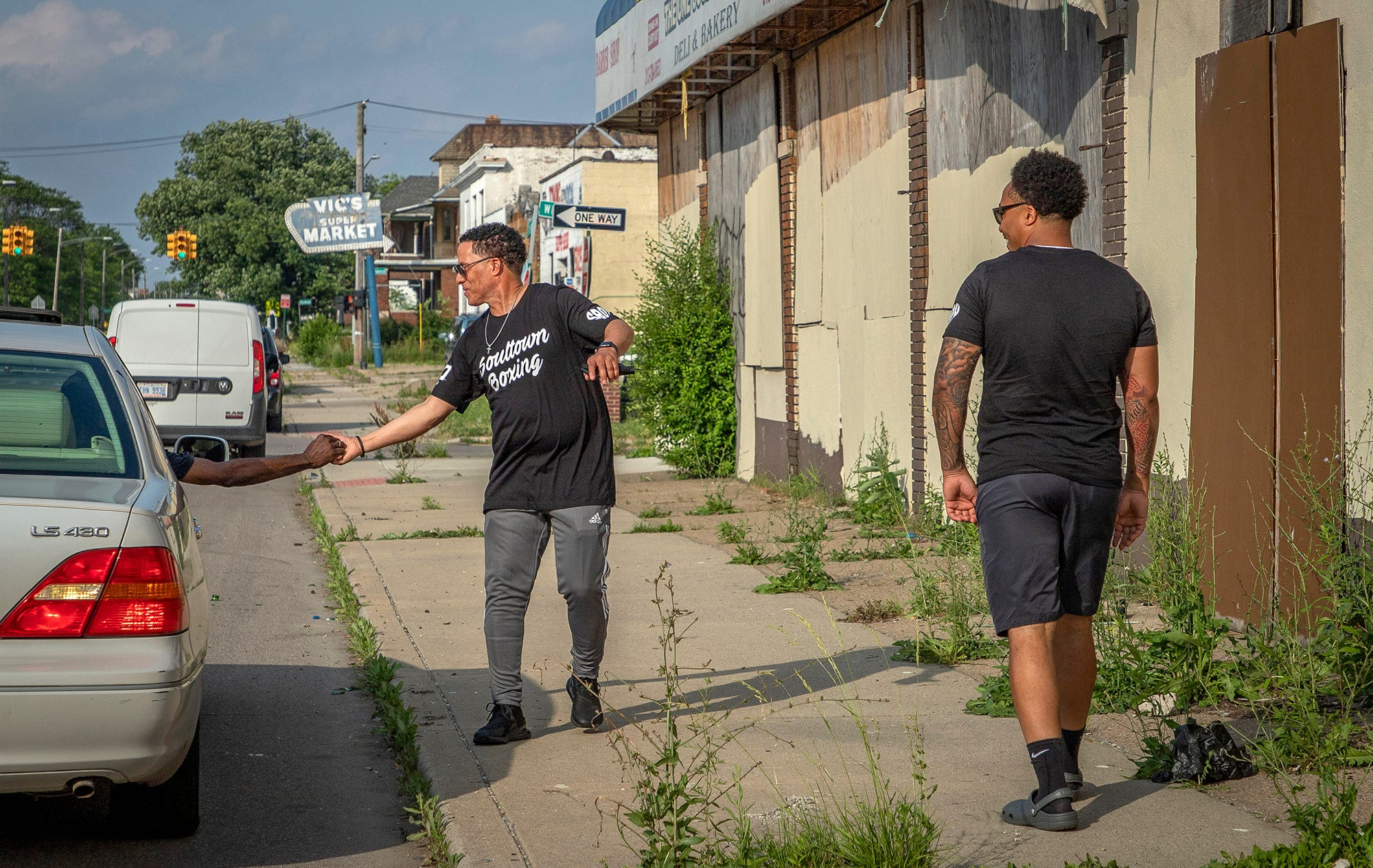 """David Woods Jr., 33, right, watches his father David 'Bing"""" Shumate, 58, reunite with a friend from the neighborhood in front of the block of businesses on Tireman Ave. where they both shared business space in Detroit on June 18, 2021. Woods' dream started almost 25 years ago when he decided to start Enjoy Detroit's father company, SBOY (Successful Brothers of Youth) Printing, inside of a dollar store owned by his father."""