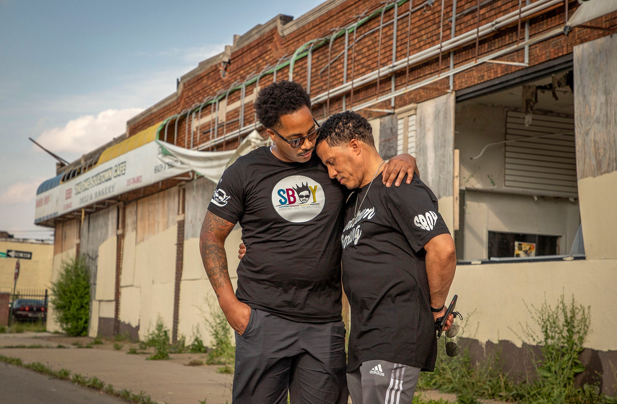 """David Woods Jr., 33, left, hugs his father David 'Bing"""" Shumate, 58, as they stand in front of the block of businesses on Tireman Ave. where they both shared business space in Detroit on June 18, 2021. Woods' dream started almost 25 years ago when he decided to start Enjoy Detroits father company, SBOY (Successful Brothers of Youth) Printing, inside of a dollar store owned by his father."""