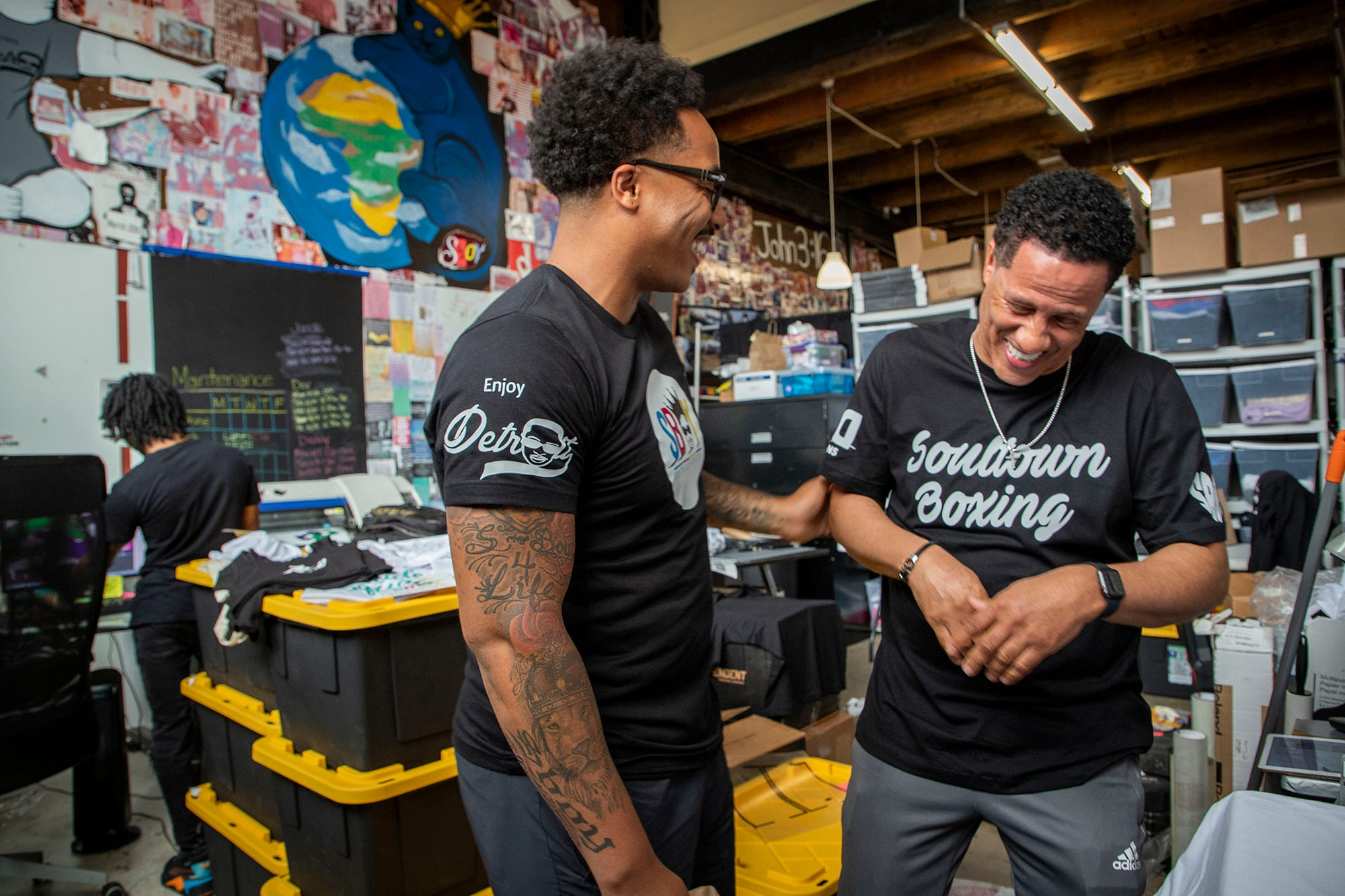 """David Woods Jr., 33, left, shares a laugh with his father David 'Bing"""" Shumate, 58, as they work making t-shirts for a customer order at his shop SBOY Printing in Detroit on June 18, 2021. Woods' dream started almost 25 years ago when he decided to start Enjoy Detroit's father company, SBOY (Successful Brothers of Youth) Printing, inside of a dollar store owned by his father."""