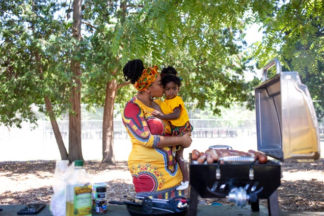 Nikita Graham kisses her daughter, Belle, as she prepares food for the Juneteenth Day celebration at Murphy Park, Saturday, June 19, 2021, in Green Bay.