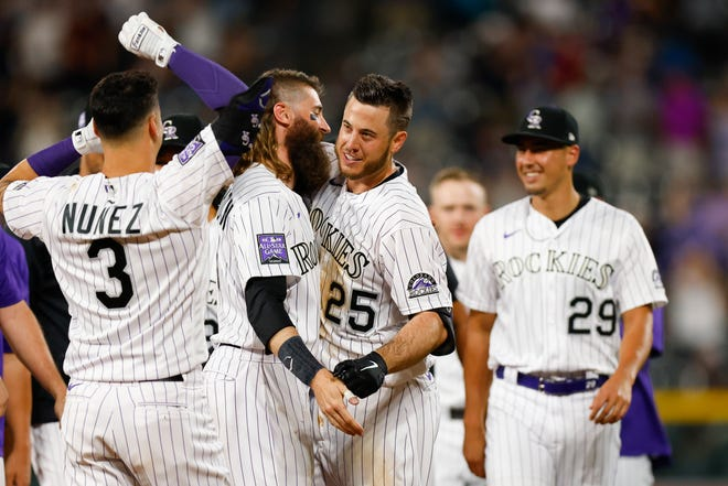 C.J. Cron (25) of the Rockies celebrates with his teammates after his game-winning RBI single in the bottom of the 10th inning against the Brewers.