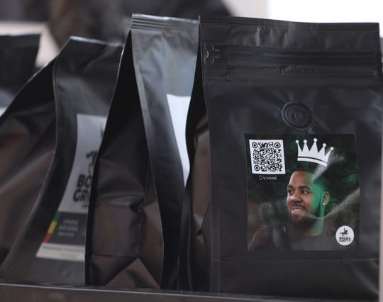 """David A. Paul, MD, is a senior neurosurgery resident and neuro-critical care fellow at the University of Rochester Medical Center, He opened a business called Bold and Gritty that makes different coffee roasts that have different images of Black men with a QR code.  Paul said he wanted to """"share a different narrative especially around Black men.""""  He and his wife, La'ren were serving coffee and selling their roasts at  Themata outdoor handmade artisan markets at the Culver Road Armory on June 19, 2021.  A local man, Daniel Snead, is featured on a bag."""