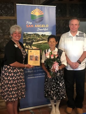 Unja Baliko (center), alongside her husband Richard, was presented a plaque by Keep San Angelo Beautiful executive director Charlotte Anderson in appreciation of Baliko's efforts in cleaning and beautifying her neighborhood for the last 10 years.