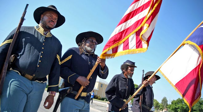Buffalo soldier reenactors lead a Juneteenth parade down Martin Luther King Drive on Saturday, June 19, 2021.