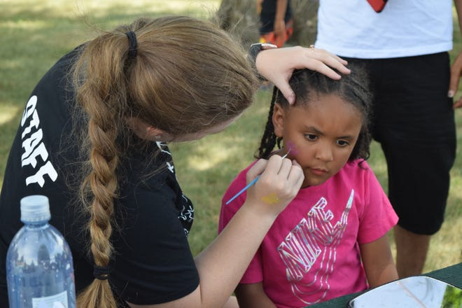 A volunteer paints a child's face at Sioux Falls' Juneteenth celebration at Terrace Park on Saturday, June 19, 2021.