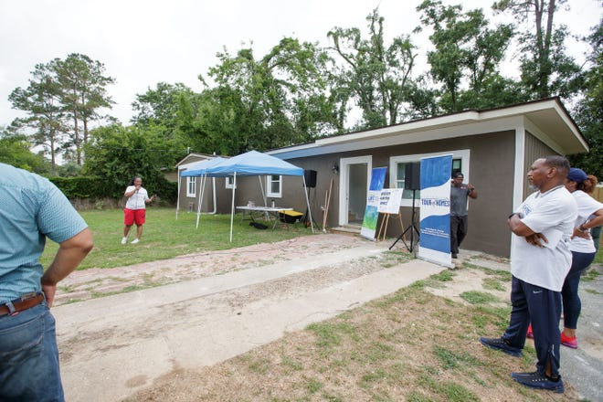 A group gathers in front of a home located on Coble Drive for an informational talk during the Southside Tour of Homes Saturday, June 19, 2021.