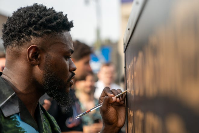 A person paints in the final letters of George Floyd's name at a statue unveiling in his honor at Flatbush Junction on June 19, 2021, in the Brooklyn borough of New York City.