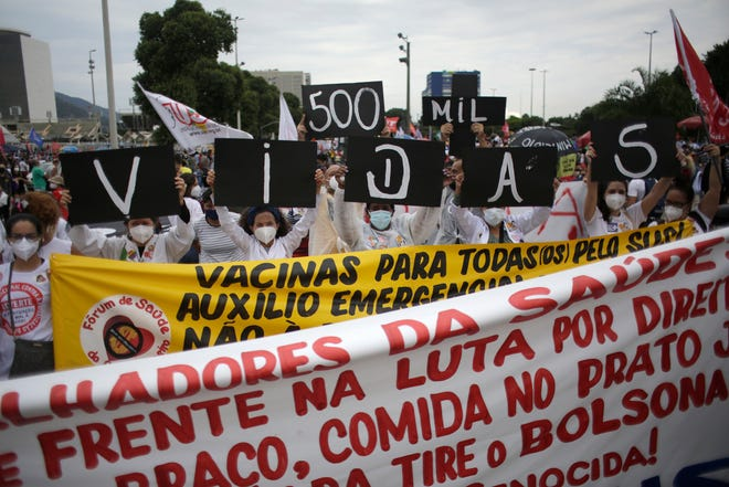 """At the same time, the women are holding posters with a message in Portuguese; """"500,000 deaths!  His mistake!"""" during a demonstration against Brazilian President Jair Bolsonar's treatment of the coronavirus and economic policy pandemic, protesters say they are harming the interests of the poor and working class, in Rio de Janeiro, Brazil, on Saturday, June 19, 2021."""