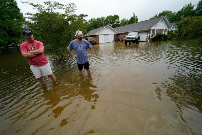 Danny Gonzales, right, stands in front of his flooded house with his neighbor Bob Neal, upset with power company trucks driving though the flooded neighborhood pushing water back into his home, after Tropical Storm Claudette passed through, in Slidell, La., Saturday, June 19, 2021.