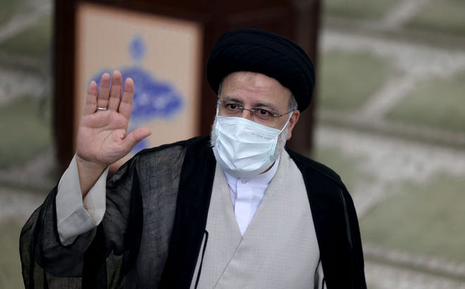 Iranian ultraconservative cleric and presidential candidate Ebrahim Raisi waves as he votes at a polling station in the capital Tehran, on June 18, 2021.