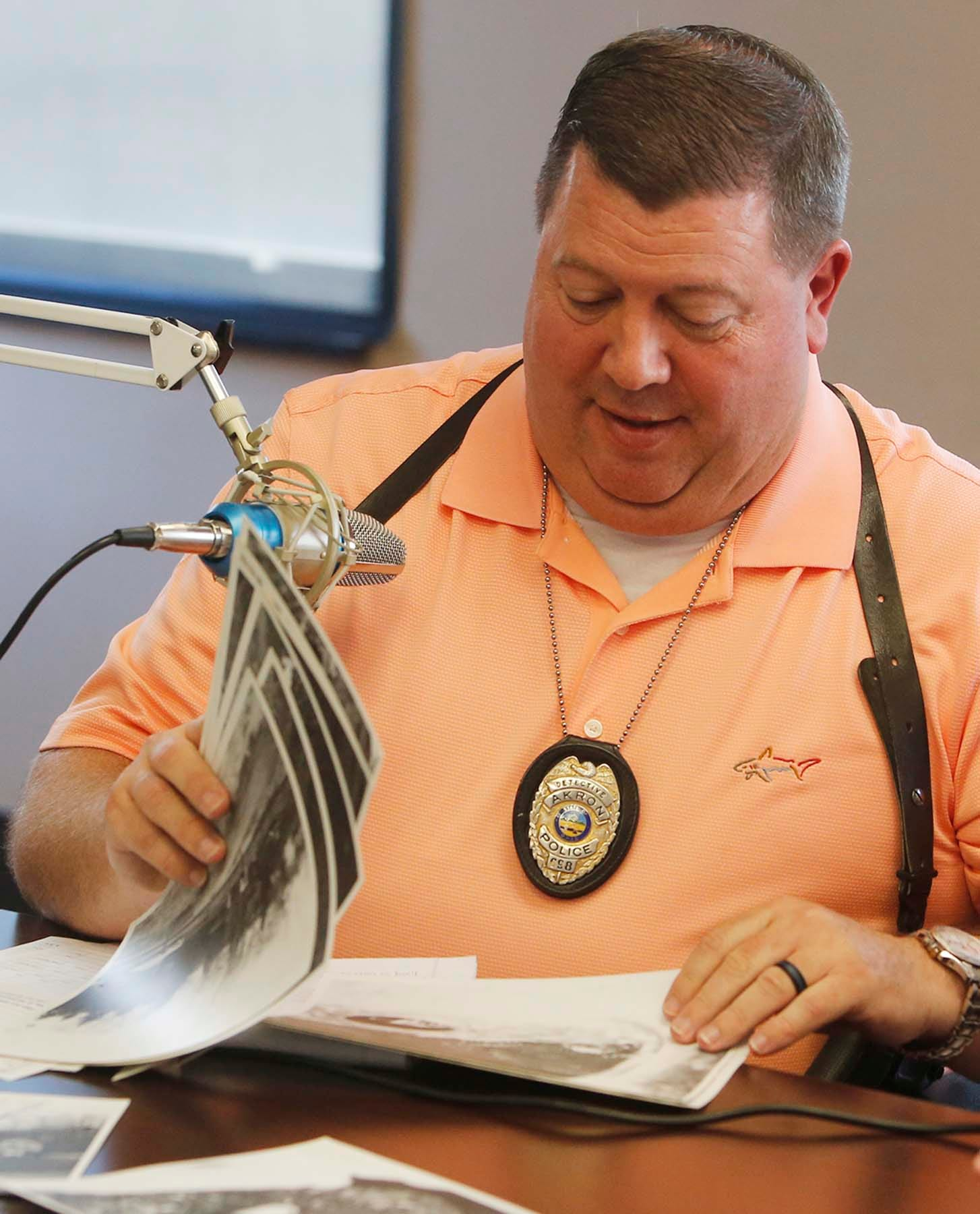 Akron Police Department Detective James Pasheilich goes through photographs in the case files of murder victim Leslie Barker. Barker was killed in 1978, and her death remains unsolved.