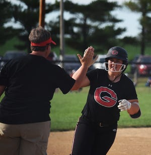Gilbert's Halli Nissen gets congratulated by head coach Staci Sniezek after belting a three-run home run in the top of the sixth inning during the Tigers' 3-1 victory over No. 12 (3A) Roland-Story at the Kiwanis Invitational in Roland Saturday. Nissen's homer gave her younger Lauren  - the starting Tiger pitcher - a big victory on her 16th birthday.