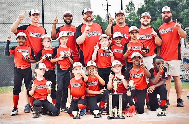The Barnwell All-Star Coaches Pitch players and coaches each hold up one finger after being declared district champs on June 15. The team now heads to the state tournament in Clemson.