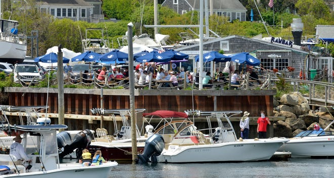 The outdoor seating at Sesuit Harbor Cafe overlooks the water and the boaters heading out of the harbor.