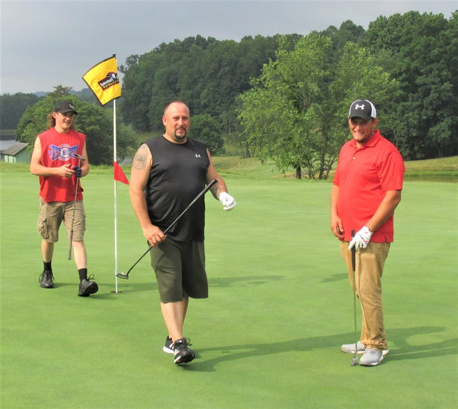 Bill Mullet (center) walks off the ninth green at Black Diamond Golf Course in Millersburg after finishing the front nine with his sons Drake (left) and Coven, who not only treated their dad to a round of golf, but bought him a new set of clubs last week for his birthday.
