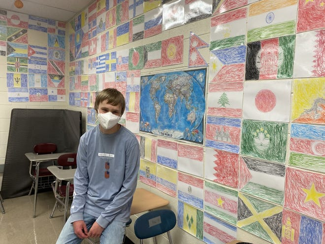 Airport High School junior Brandon St. John stands with a portion of the 213 country flags he drew that are on display in Dana Paul's classroom.