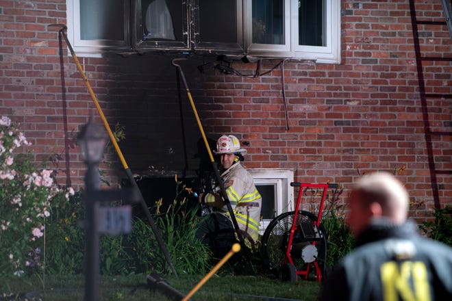 Natick Deputy Fire Chief Vic Lipomi works near a basement window following a two-alarm fire at 9½ Franconia Ave. in Natick, June 19, 2021.