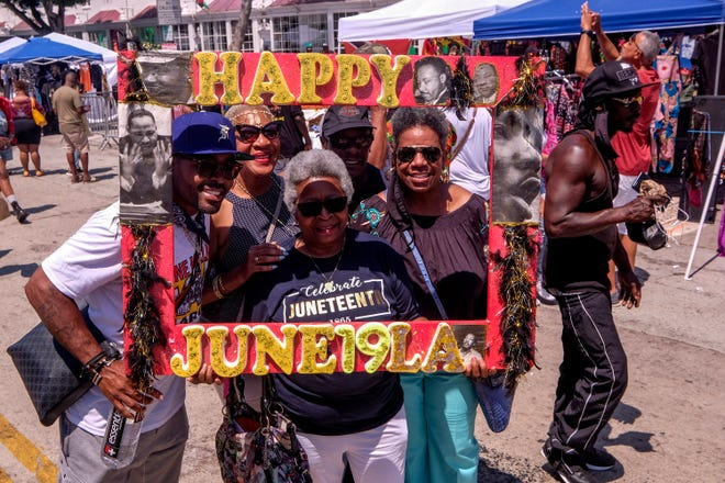People pose with a frame as they celebrate during a Juneteenth commemoration at Leimert Park Plaza on Saturday in Los Angeles. Hundreds of people descended on Leimert Park to take in the festival, and for many, the mood was jubilant.