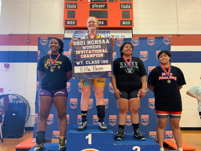 Burns' Ella Beam proudly holds up a sign saluting her as the state's 195-pound girls wrestling champion.