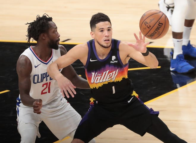Phoenix Suns guard Devin Booker (1) is defended by LA Clippers guard Patrick Beverley (21) during Game 1 of the Western Conference Finals in Phoenix June 20, 2021.