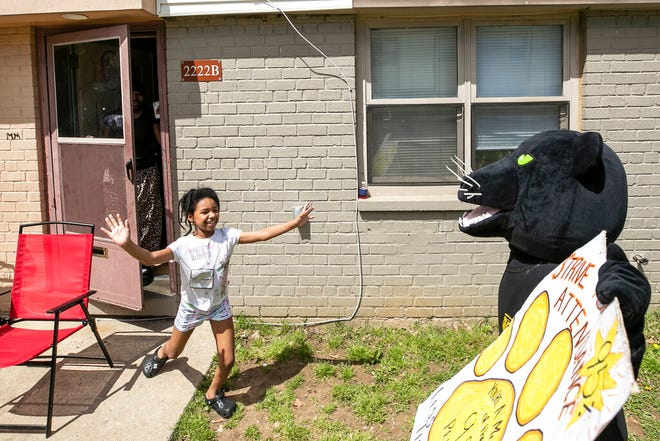 Student Zikirah Skinner runs towards Lisanne Brown, dressed up as a Panther, the mascot of William Dick Elementary, during a surprise visit to her home to celebrate high attendance in North Philadelphia on Thursday, May 6, 2021. (Heather Khalifa/The Philadelphia Inquirer via AP)