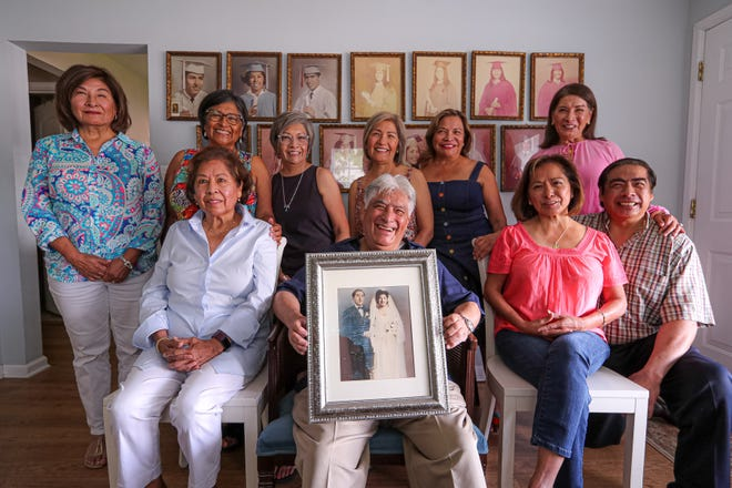 Ten of Josefina Zamarripa's 13 surviving children pose with Josefina and Guillermo Zamarripa's 1945 wedding photo. Josefina died on May 2 at the age of 92. After Guillermo's death in 1964, Josefina raised her children in a two-bedroom house in East Austin. All of the 13 surviving kids graduated from high school and eight from college.