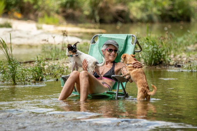 """Rona Distenfeld cools off with her dogs in Onion Creek on Monday. When asked about the high heat index, she said, """"I don't care. I'm sitting in the water."""""""