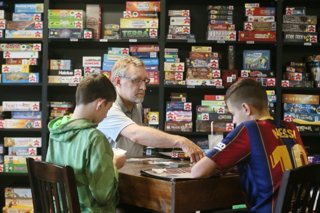 Chris Wilms and his sons Owen, 12 and Alex, 15 play a card game called Boss Monster at the Malted Meeple on Saturday June 19, 2021 in Hudson.